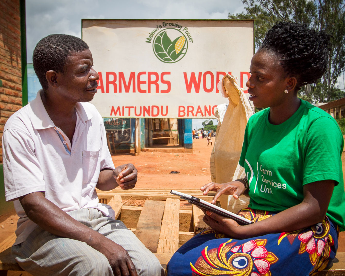 An FSU extension worker interviews a farmer outside one of the Farmer World shops